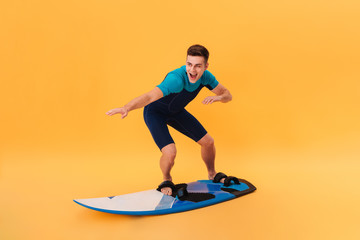 Picture of a Happy surfer in wetsuit using surfboard