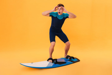 Picture of a Shocked surfer in wetsuit using surfboard