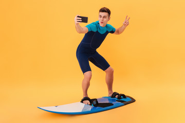 Image of Happy surfer in wetsuit using surfboard
