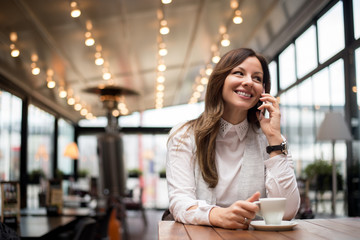 Young happy woman talking on mobile phone with friend while sitting alone in modern coffee shop interior.