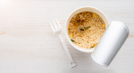 Instant noodle cup on wooden table,Top view,Selective focus on Instant noodle