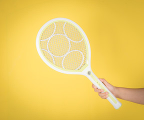 Hand holding rechargeable mosquito swatter on yellow background.