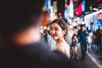 Portrait of young woman outdoors by night, Tokyo, Japan