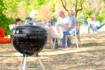 Barbecue grill and happy family on background outdoors