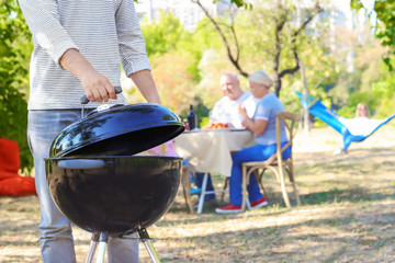 Man cooking on barbecue grill outdoors