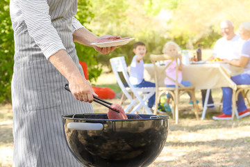 Man cooking tasty steaks on barbecue grill outdoors