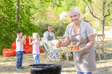Mature woman cooking vegetables on barbecue grill outdoors