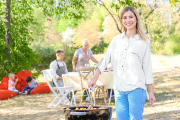 Woman cooking tasty steaks and vegetables on barbecue grill outdoors