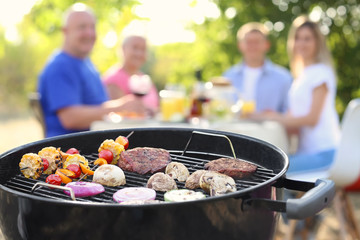 Barbecue grill with tasty steaks and happy family on background outdoors