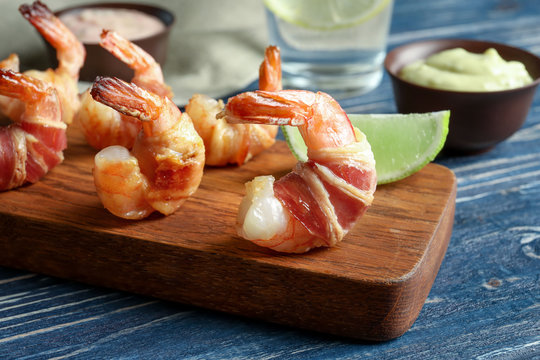 Board with shrimps wrapped in bacon on table