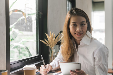 Young business woman in white dress sitting at table in cafe and writing in notebook. Asian woman using tablet and cup of coffee. Freelancer working in coffee shop. Student learning online.