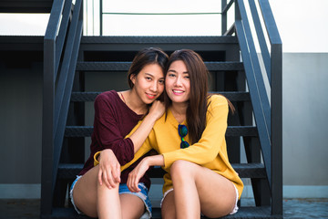LGBT lesbian women couple moments happiness. Lesbian women couple together outdoors concept. Lesbian couple embraced together relation fall in love. Two asian women having fun together at rooftop.