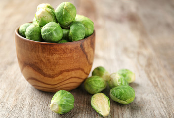 Bowl with raw Brussels sprouts on wooden background