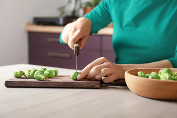 Young woman cutting fresh raw Brussels sprouts on board in kitchen