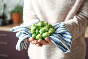 Woman with fresh raw Brussels sprouts in kitchen