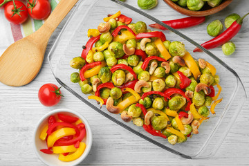 Glass dish with baked Brussels sprouts, pepper and nuts on table