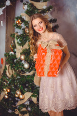 Pretty happy young woman in beautiful lace pastel dress celebrate christmas at home. Christmas concept, female fashion. Lady in romantic dress posing in cozy apartments decorated for New year