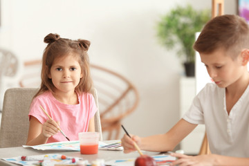 Little children painting at table