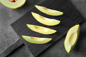 Wooden board with yummy melon slices on table