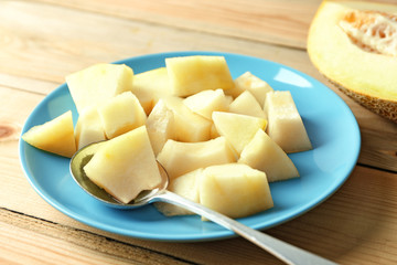 Plate with yummy melon on wooden table