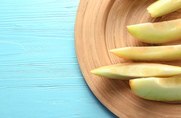 Plate with yummy melon slices on wooden table