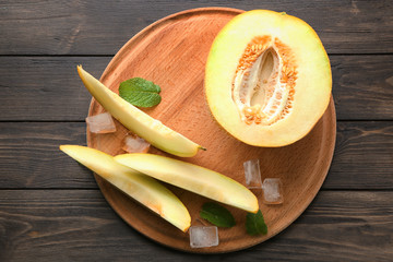 Board with yummy melon on wooden table