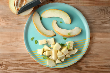 Plate with sliced yummy melon on wooden table