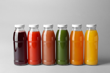 Bottles with juices on light background