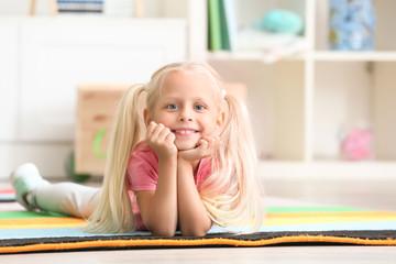 Cute little girl lying on floor in kindergarten
