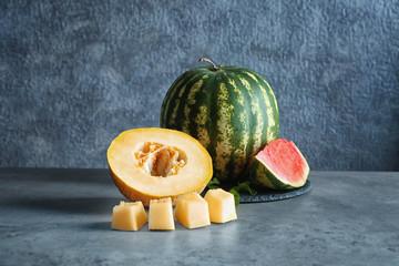Yummy fresh melon and watermelon on grey background