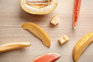 Slices of yummy fresh melon and watermelon on wooden table, top view