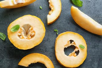 Yummy cut melon on grey background, top view