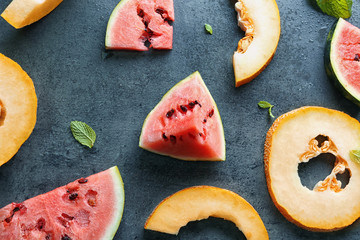 Yummy cut melon and watermelon on grey background, top view