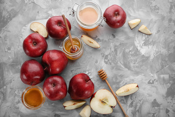 Delicious red apples and honey on table