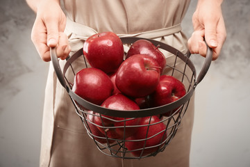 Woman holding basket with delicious red apples, closeup