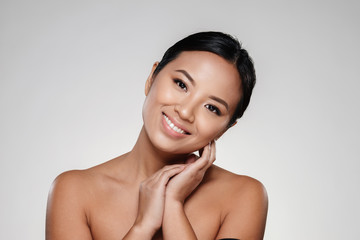 Smiling asian lady touching her clear skin and looking camera