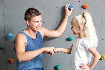 Little girl and instructor in climbing gym