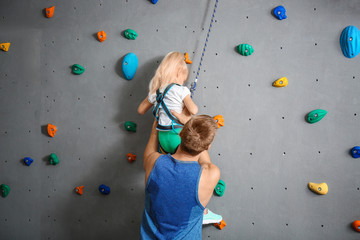 Instructor helping little girl climb wall in gym