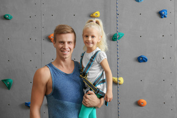 Instructor holding little girl in climbing gym