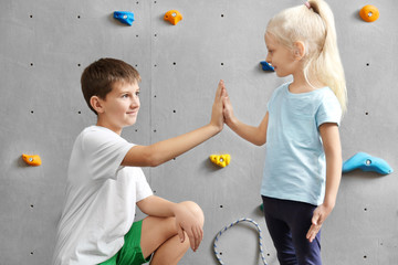 Little girl and young boy in climbing gym