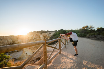 Man stretching at sunset on a cliff