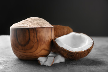 Wooden bowl with coconut flour and fresh nuts on table
