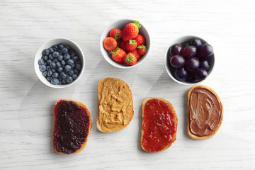 Slices of bread with jam, peanut butter and chocolate paste on light background