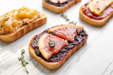 Slice of bread with jam and grapefruit on table