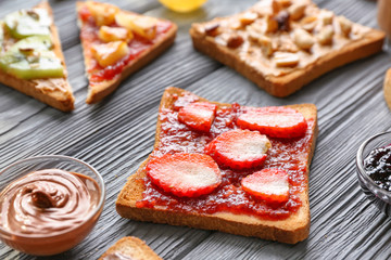 Slice of bread with jam and strawberry on table