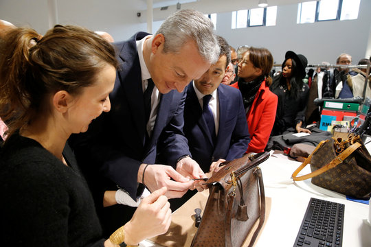"""French Finance Ministern Bruno Le Maire and Minister for Public Action and Accounts Gerald Darmanin, check a leather luxury bag as they visit the new logistic hub of """"Vestiaire Collective"""" an online marketplace in Tourcoing"""