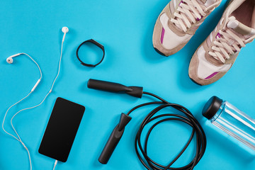 Flat lay shot of Sport equipment. Sneakers, jump rope, earphones and phone on blue background.