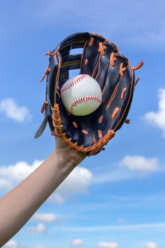 Arm holding baseball with glove  in blue sky