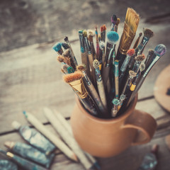 Paintbrushes in a jug from potters clay, wooden palette and paint tubes.