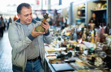 Positive elderly man choosing interesting souvenirs at traditional flea market